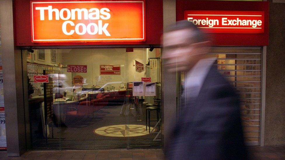 A passerby rushes pass the British based travel retailer and foreign exchange dealer Thomas Cook which has sold it Australian and New Zealand operations, ending a 120-year-presence down under in Sydney, 12 December 2000.