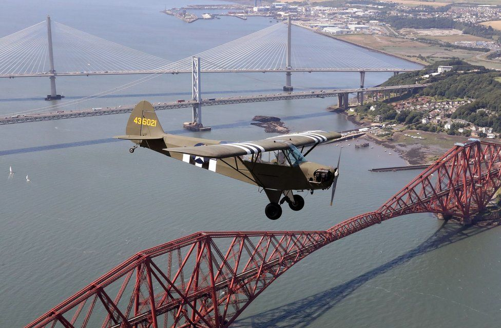 """Jim McTaggart takes his 1940 Piper Cub, with its US Army D-Day reconnaissance aircraft markings, for a practice flight over the Forth Rail Bridge,Forth Road Bridge and the new Queensferry Crossing ahead of the aircraft""""s appearance at ScotlandÕs National Airshow at East Fortune, East Lothian on Saturday 22 July."""