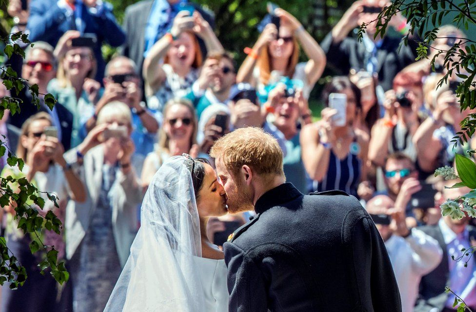 """Meghan Markle and Prince Harry kiss on the steps of St George""""s Chapel at Windsor Castle following their wedding. Saturday May 19, 2018"""