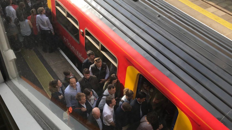 Commuters trying to get on an overcrowded train at Putney