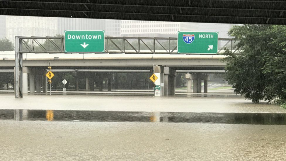 """Flooded street below a sign to """"Downtown"""""""