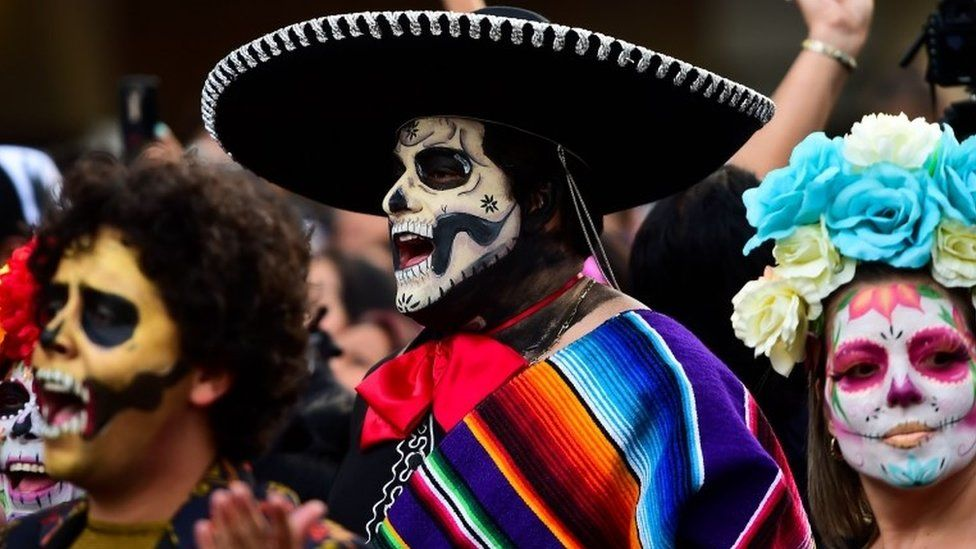 A man wears a colourful poncho and a sombrero during the Catrinas parade in Mexico City
