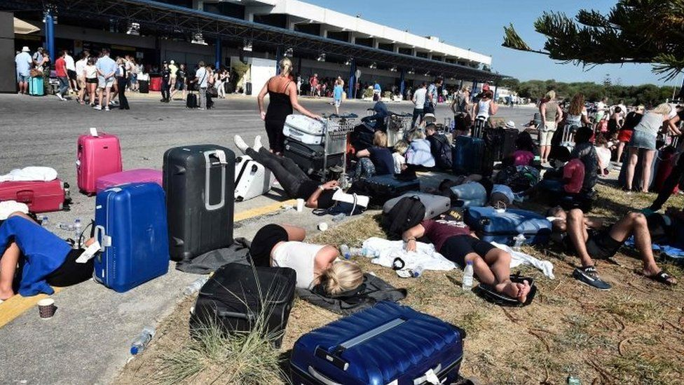 Tourists gather outside terminal buildings at an airport on the island of Kos on July 21, 2017, after flights were cancelled following a 6.5 magnitude earthquake