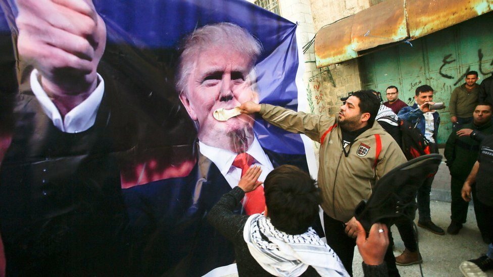 Palestinians hit a banner bearing the face of Donald Trump with shoes during a protest in the West Bank city of Hebron on 24 February 2017