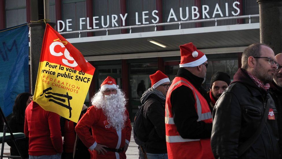 SNCF railway workers serve Christmas dinners in front of the Les Aubrais station near Orleans, central France, 23 December 2019