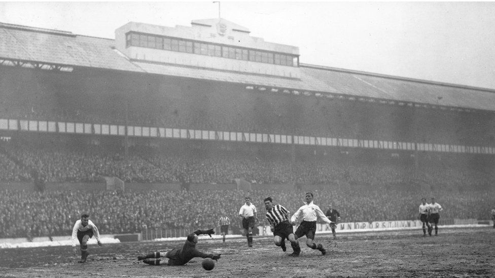 18th January 1936: Spurs goalkeeper, Taylor, deflects a goal bound shot with his finger tips from Sheffield player, Dodds, as Tottenham Hotspur play Sheffield United at White Hart Lane.