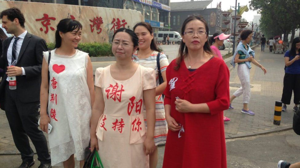Wives protesting outside the top prosecutor with husbands' names stuck on dresses