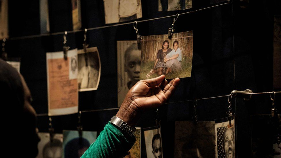 """This file photo taken on April 29, 2018 shows a visitor looking at victims"""" portraits at the Kigali Genocide Memorial in Kigali, Rwanda"""