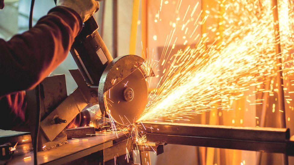 Worker using electric grinder