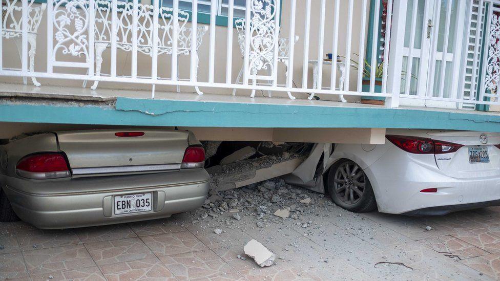 Una casa colapsada encima de dos autos.
