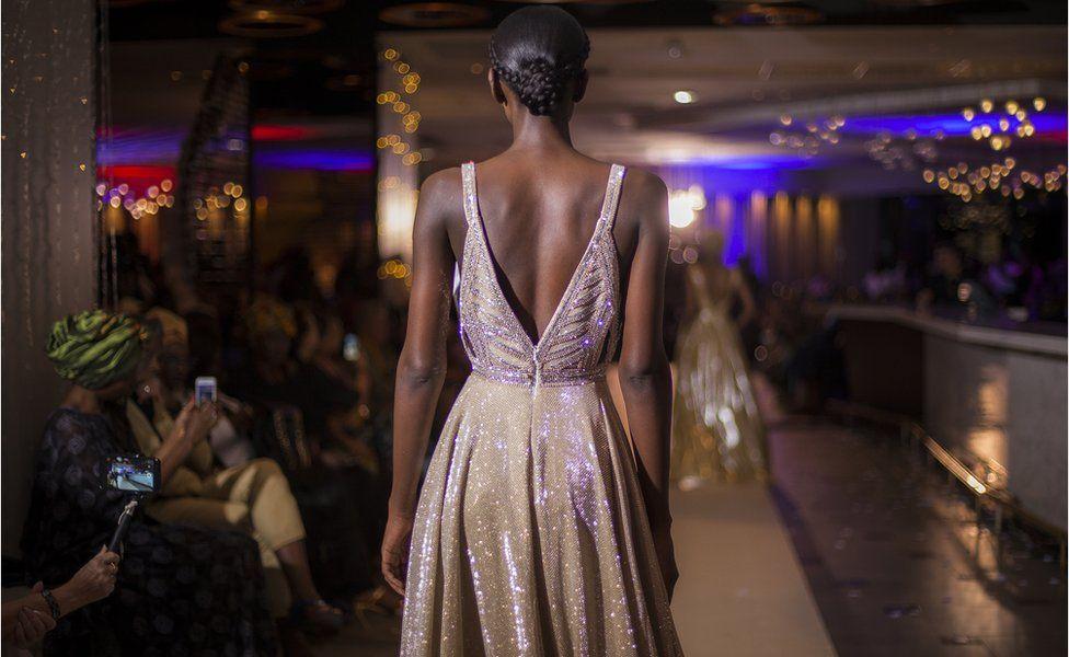 Un mannequin marchant sur le podium au défilé de mode à l'hôtel Pullman Teranga pendant la Semaine de la mode de Dakar à Dakar, Sénégal.