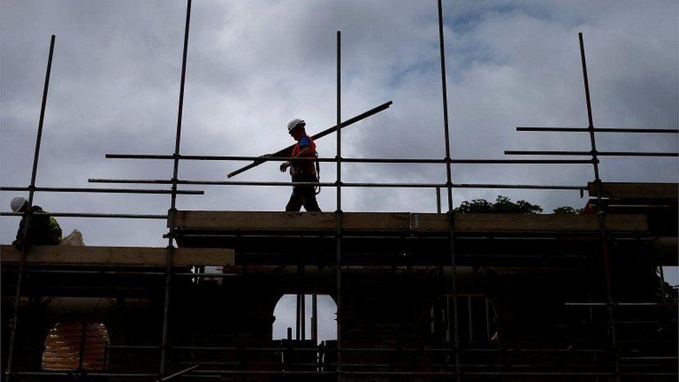 Builder assembling scaffolding