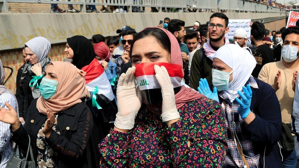 Protesters wearing face masks take part in a demonstration on International Women's Day in Baghdad (8 March 2020)