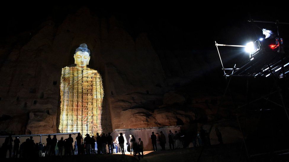 People watch a 3D projection of the 56 metre-high Salsal Buddha at the site where the Buddhas of Bamiyan statues stood before being destroyed by the Taliban in March 2001.