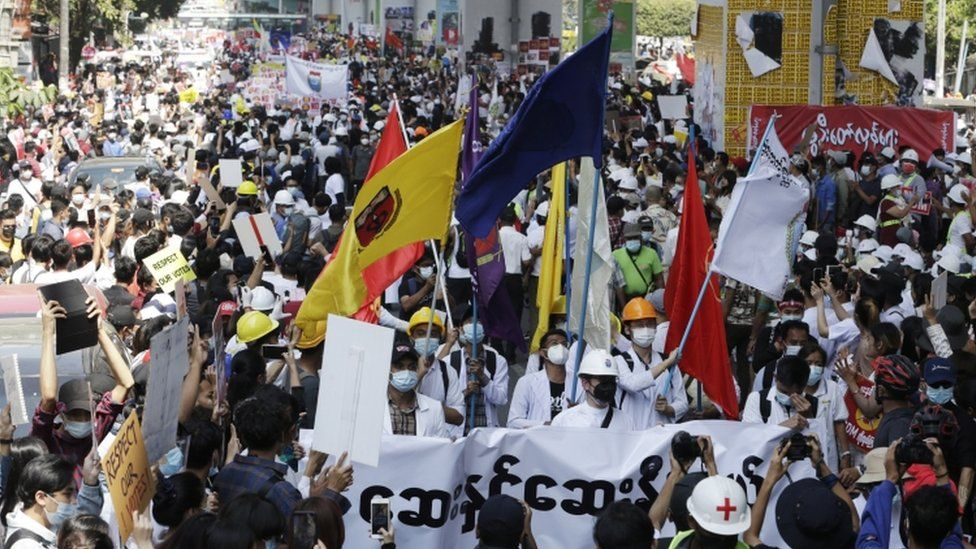 Demonstrators hold flags during a protest against the military coup, in Yangon, Myanmar
