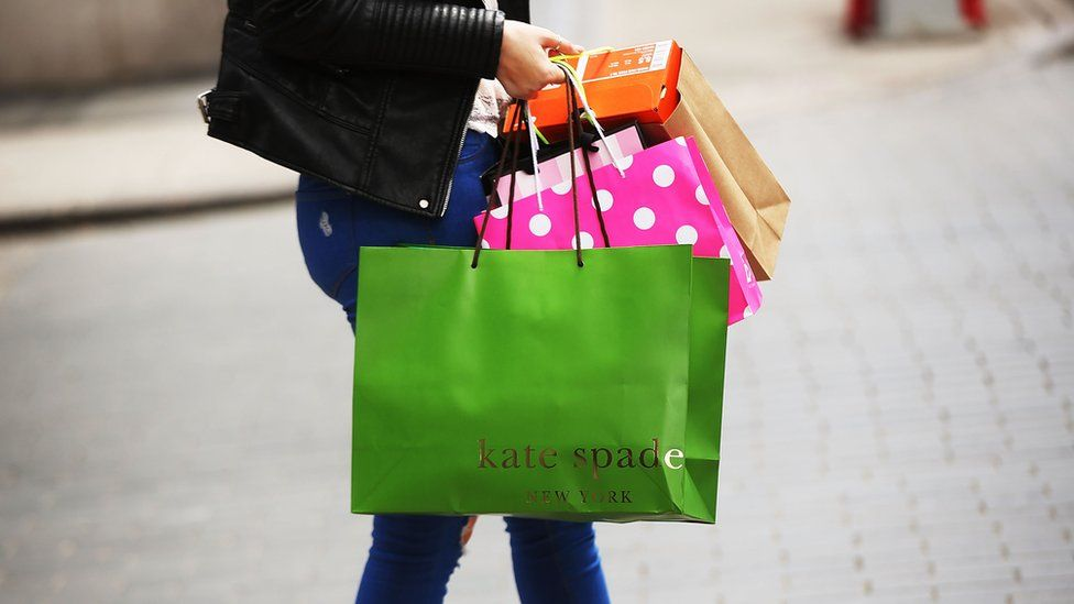 A woman walks out of a Kate Spade store in the SoHo neighborhood of Manhattan.