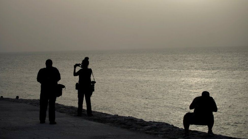"""Photographers shoot pictures at the colonial-era fortress """"El Morro Cabana"""" as dust carried by winds from the Sahara desert shrouds Havana, Cuba, June 24, 2020."""