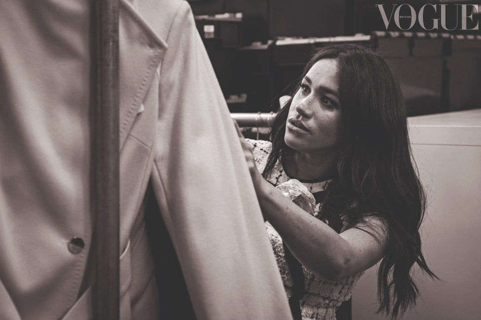 Meghan Markle, the Duchess of Sussex, looking at a rail of clothes