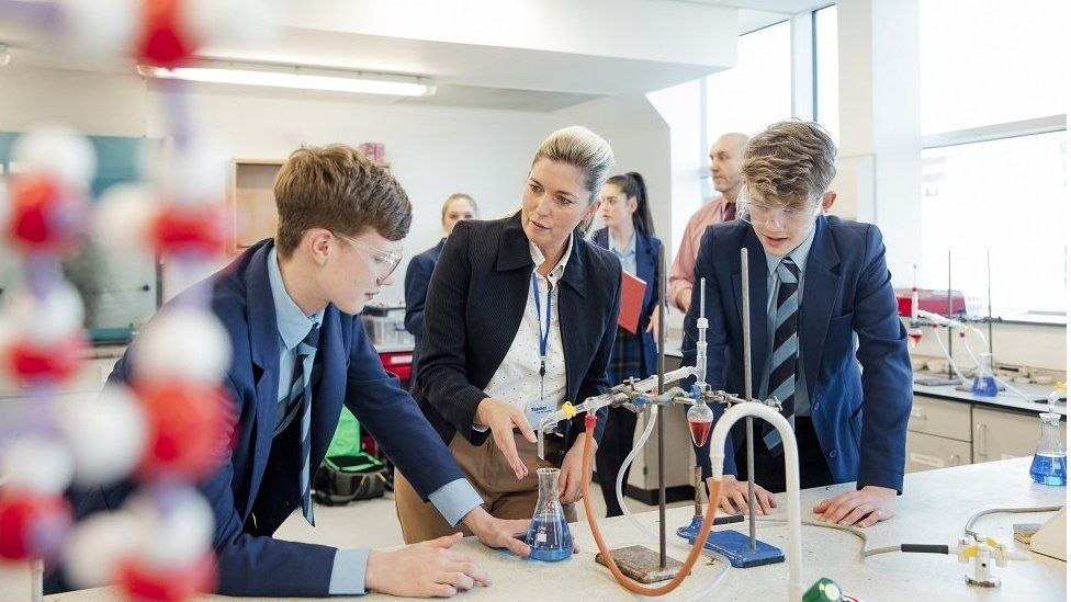 Teacher with pupils in science lab