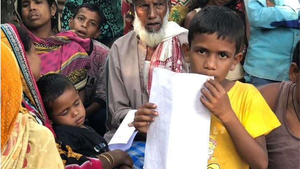 A boy holding up his documentation papers in Assam