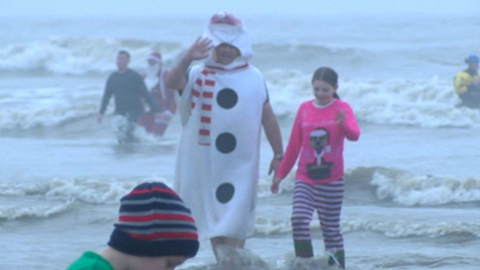 A man dressed as a snowman in the sea