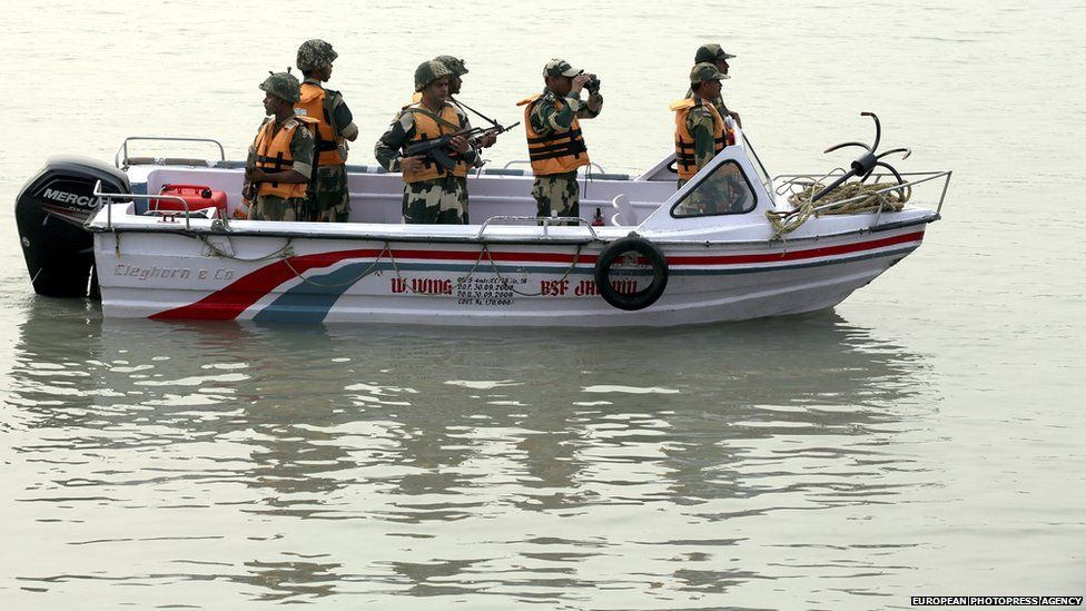 Indian Border Security Force (BSF) soldiers on a boat patrol on the Chenab river near the India-Pakistan international border