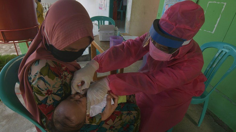 A health worker gives a vaccine to a child in Indonesia