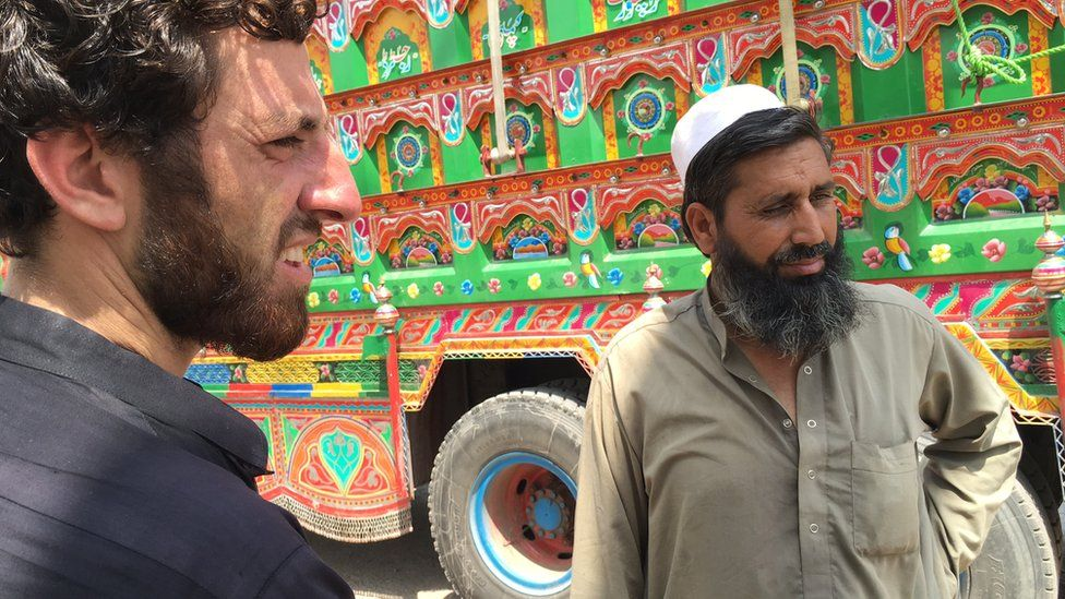 Noor Mohammad, right, beside a truck
