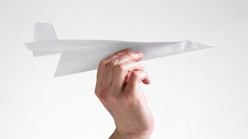 Hand holding paper aeroplane