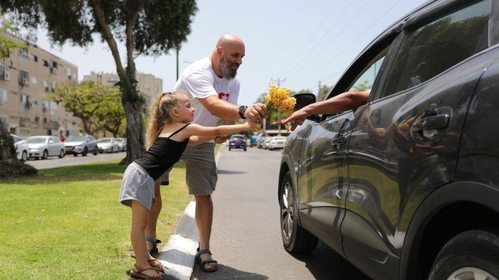Israelis hand out flowers in Ashkelon on the first day of the ceasefire