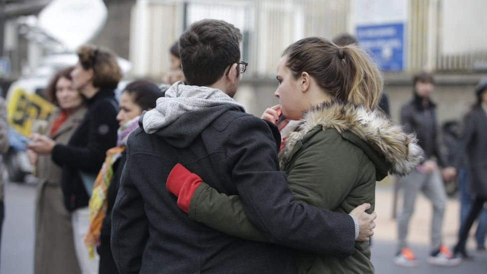 Mourners gather outside of the Carillon bar in the 10th district of Paris on November 14, 2015, following a series of attacks in and around the city, leaving at least 120 people killed.