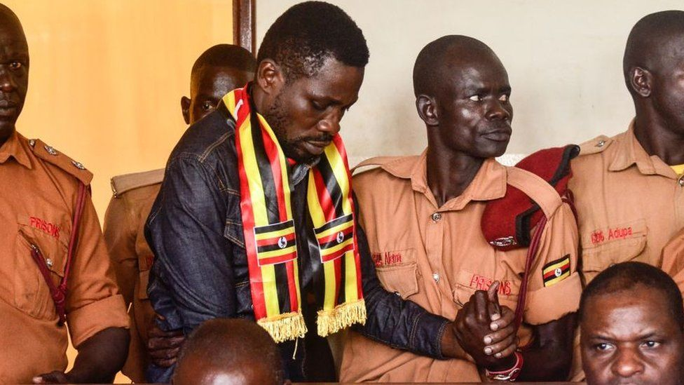 Uganda's prominent opposition politician Robert Kyagulanyi known as Bobi Wine (C) appears at the chief magistrate court in Gulu, northern Uganda, on August 23, 2018