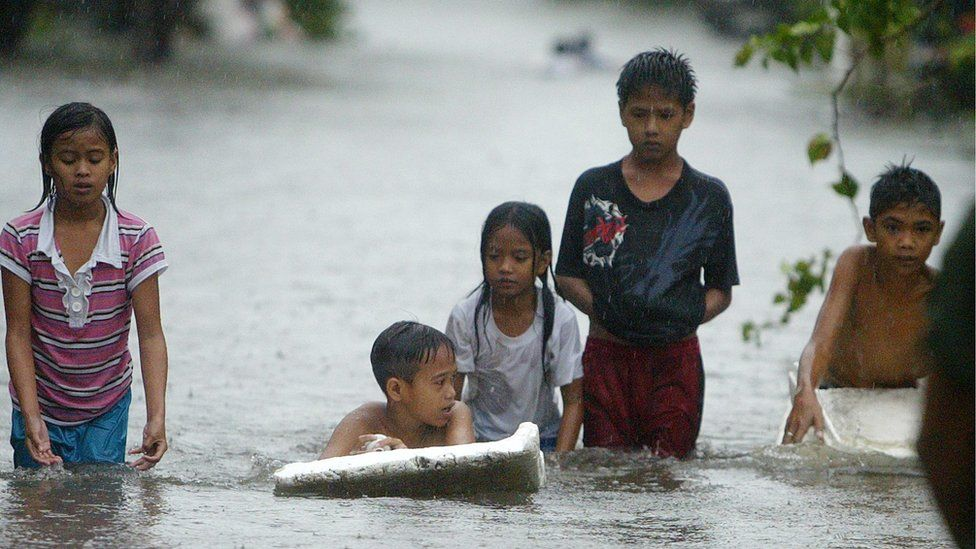Children wade through floodwaters in the Philippines