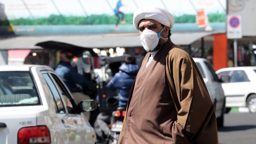 A cleric wearing a face mask walks on a street in Tehran (9 March 2020)