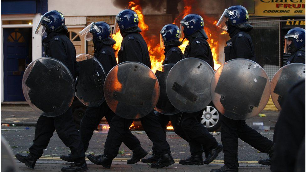Police officers in riot gear near a fire in the street