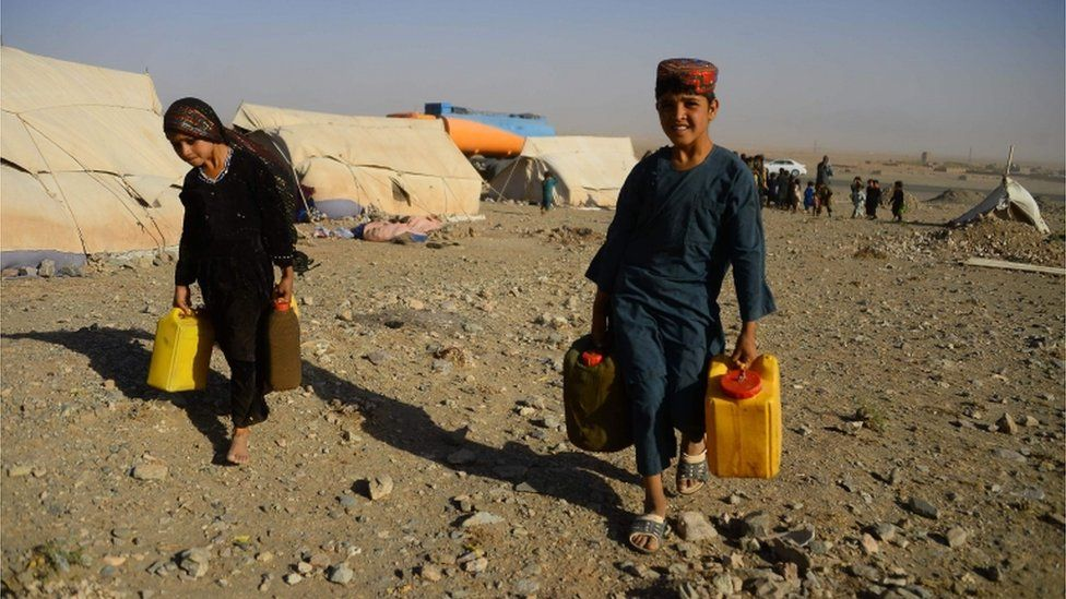 In this photo taken on August 3, 2018, drought-displaced Afghan children carry water containers filled from a tanker at a camp for internally displaced people in Injil district of Herat province