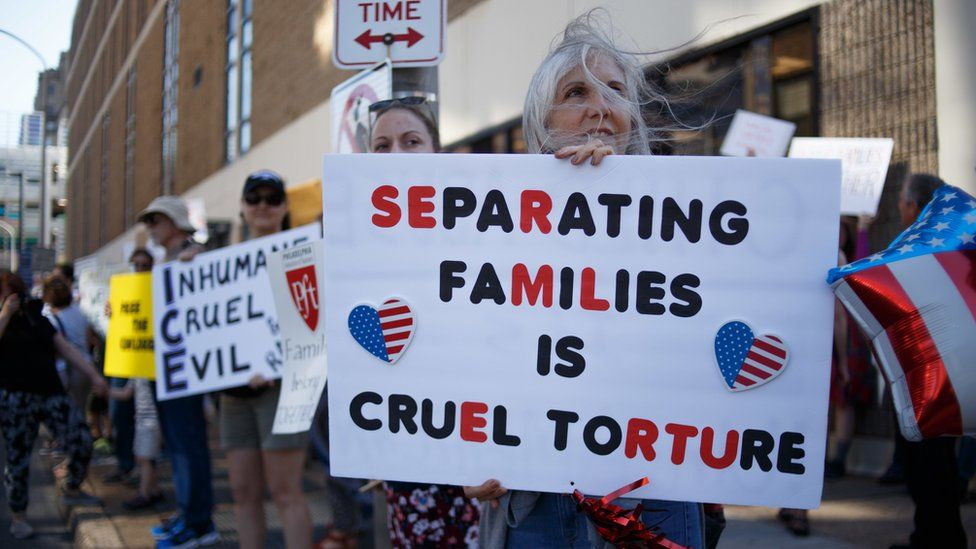 "A woman holds a sign saying ""separating families is cruel torture"""