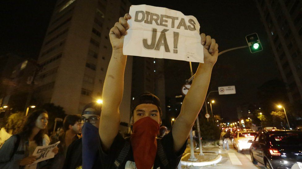"""A man holds a sign that reads """"Elections now"""" during a protest against President Michel Temer in Sao Paulo, Brazil, Sunday, Sept. 4, 2016."""