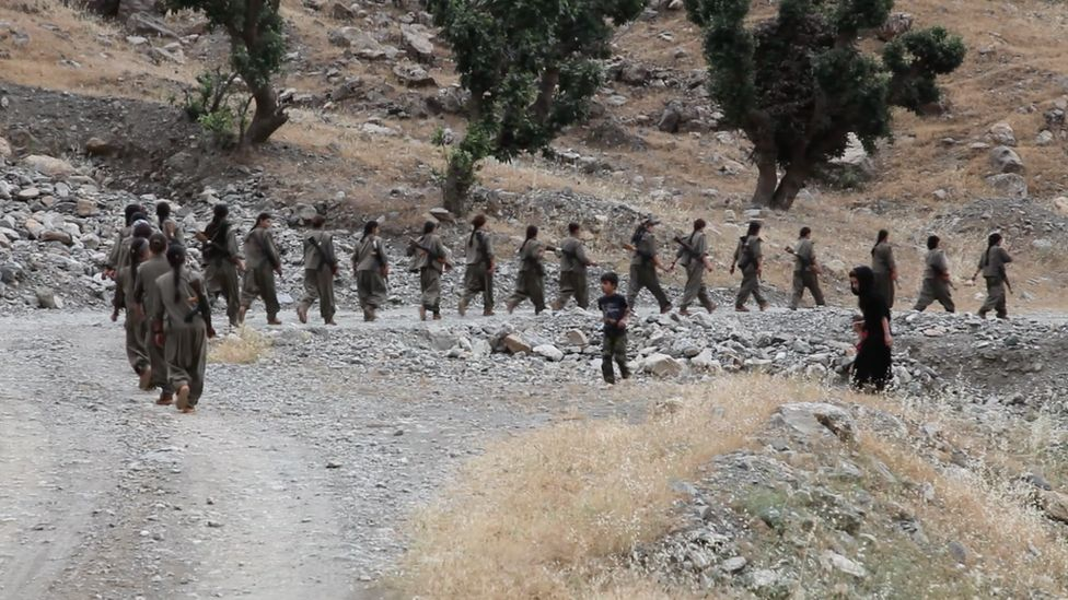 PKK fighter march from their base in Iraq towards the frontline with Islamic State in Syria