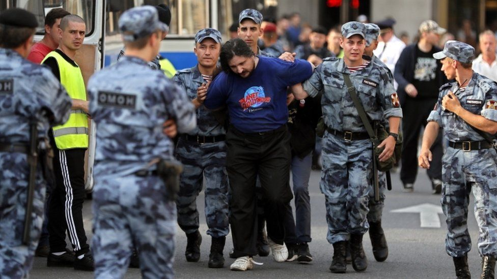 A protester is arrested by uniformed police officers on 9 September 2018.