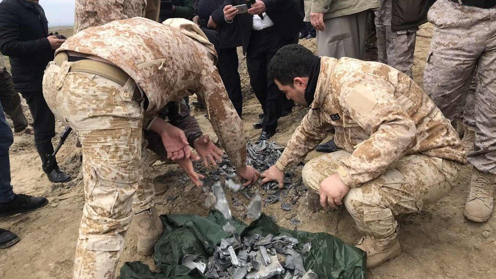 Iraqi security forces find and collect the pieces of missiles