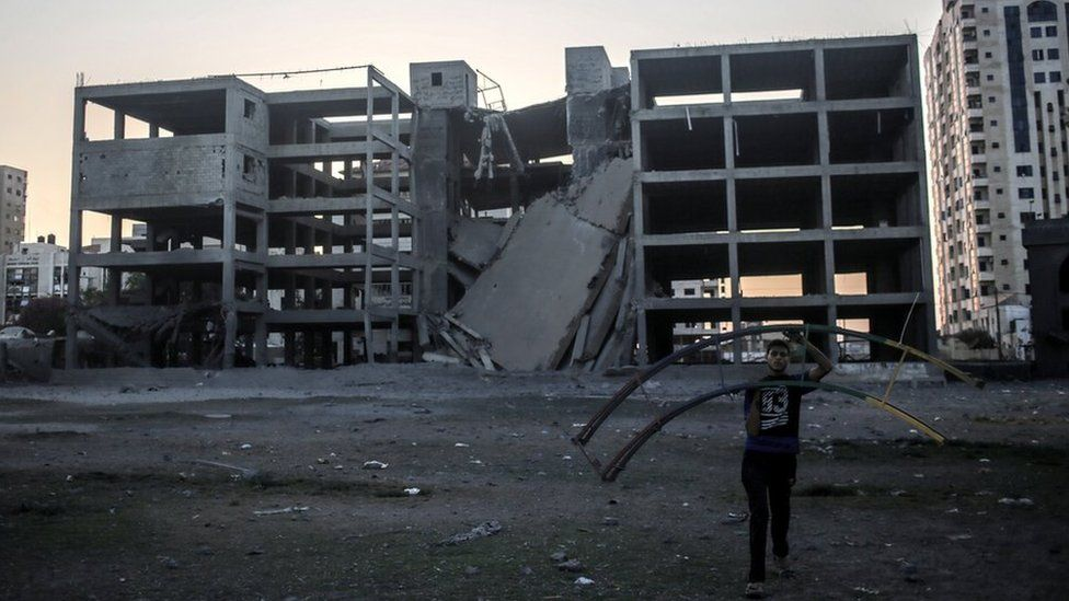 A Palestinian carries a destroyed swing at the park near a building after Israeli air strikes, at central Gaza City, 14 July 2018