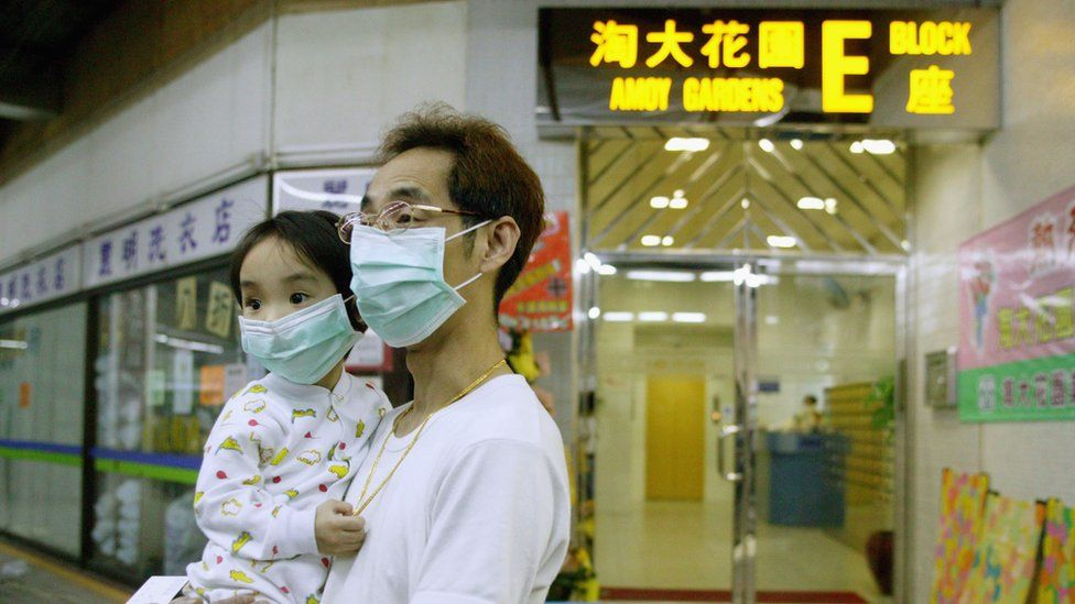 A man holds child outside of Amoy Gardens block in Hong Kong in 2003