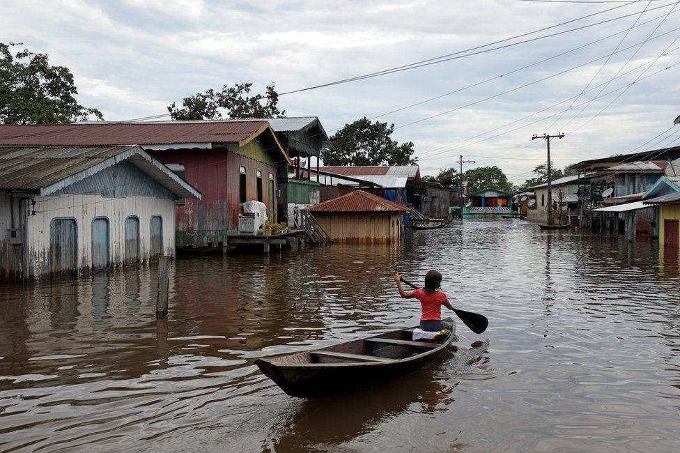 A girl paddles her canoe through a street flooded by the rising Solimoes river