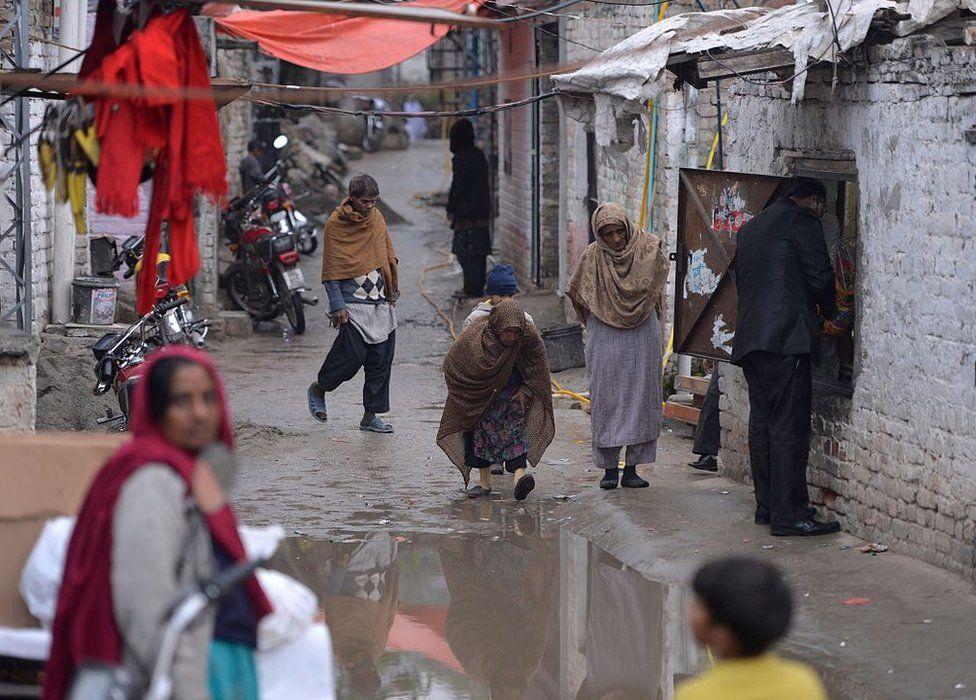 Pakistani Christians walk down a street in a slum Christian neighbourhood in Islamabad on December 10, 2015.