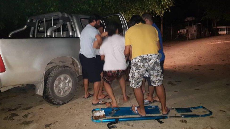 Men at the camp lifting a collapsed refugee into a PNG immigration car