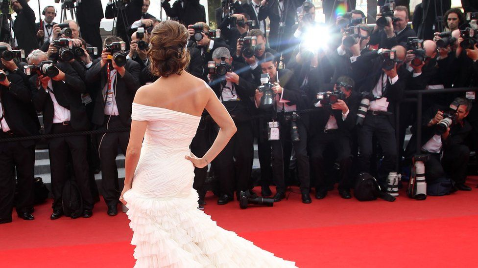 Paparazzi line up to photograph a celebrity at a red-carpet event