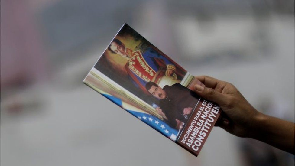 A supporter of Venezuelan President Nicolas Maduro shows a document on the National Constituent Assembly during a rally in Caracas, Venezuela, July 24, 2017.