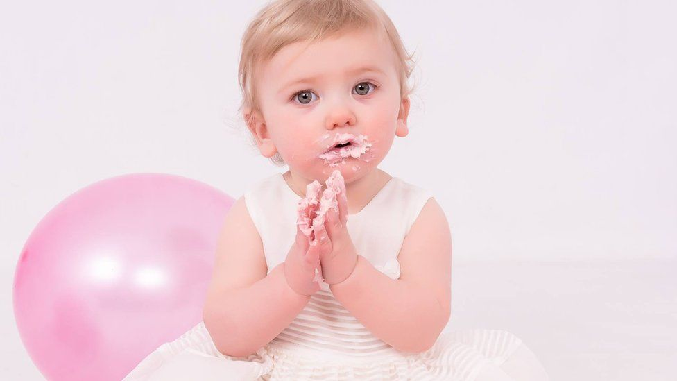 Baby Elora has her hands full of icing from a cake