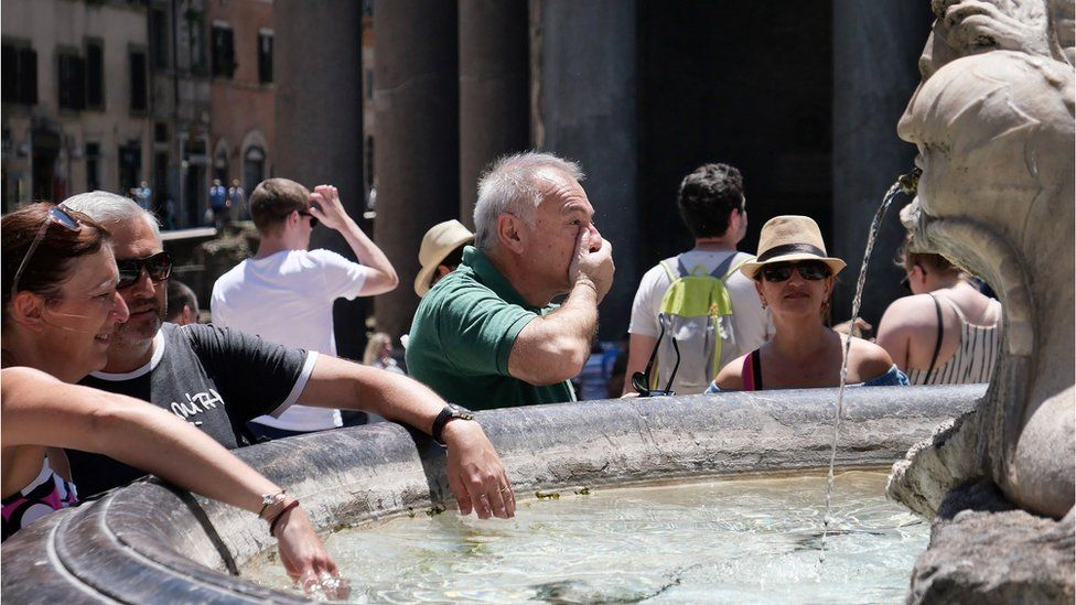 Tourists refresh at a fountain in front of the Pantheon monument during an unusually early summer heatwave in Rome, 24 June 2019